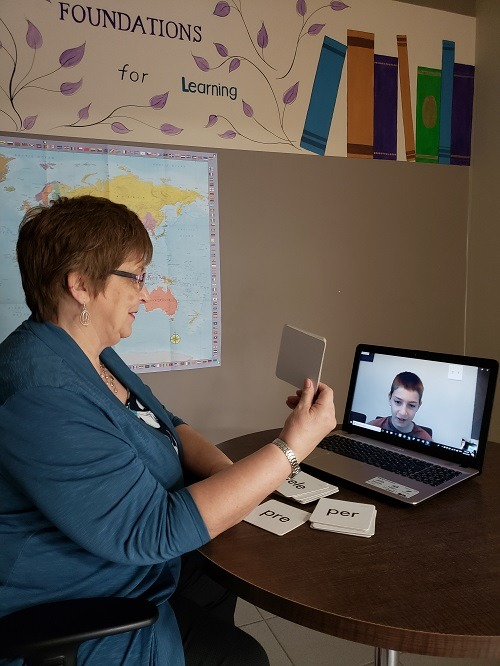 A photo of Sharon Prest, owner of Foundations for Learning, teaching a student through Distance Learning on her laptop.
