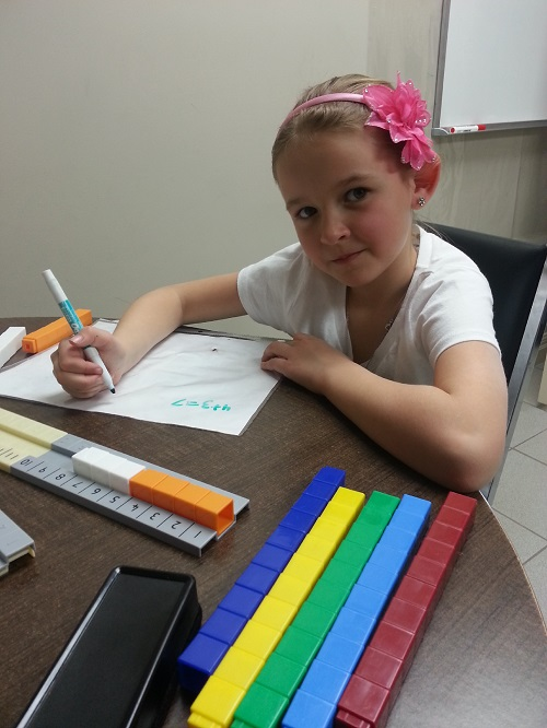 A photo of a young student at Foundations for Learning practicing math and counting.