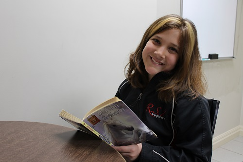 A photo of a smiling young student learning to read and understand language at Foundations for Learning