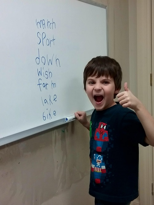 A photo of a young student at Foundations for Learning practicing reading and spelling, and learning how to spell.