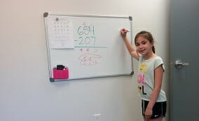 A young and happy student practicing math on a whiteboard at Foundations for Learning