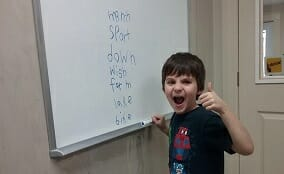A photo of an excited young student learning how to spell and read at Foundations for Learning